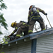 Firefighters ventilating the roof of a home